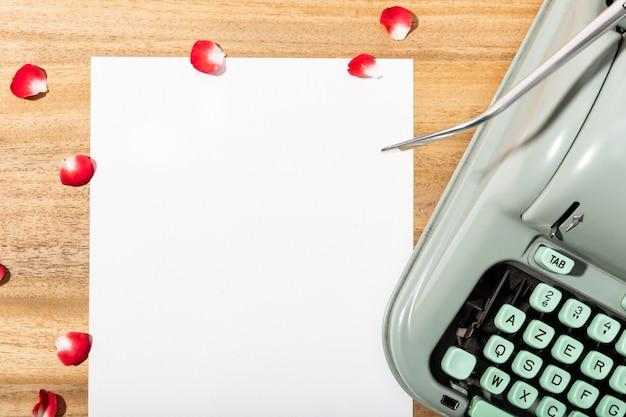 List miłosny. biurko z czystym papierem, retro maszyną do pisania i czerwonymi płatkami róży