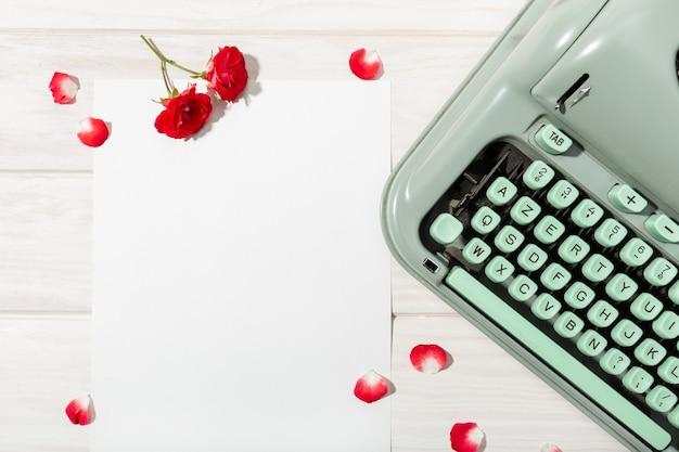 List miłosny. biurko z czystym papierem, retro maszyną do pisania oraz czerwonymi różami i płatkami