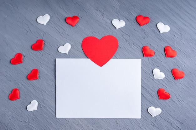 List miłosny, walentynka dla bliskich. pusta biała kartka papieru otoczona białymi i czerwonymi kształtami serca na szarym modnym tle