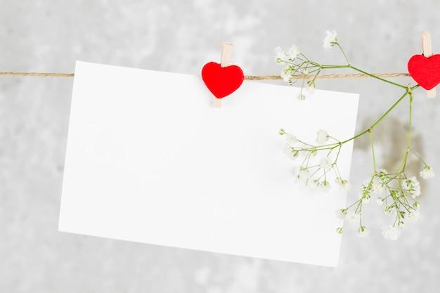 List miłosny wisi na linie i kwiat na jasnym tle