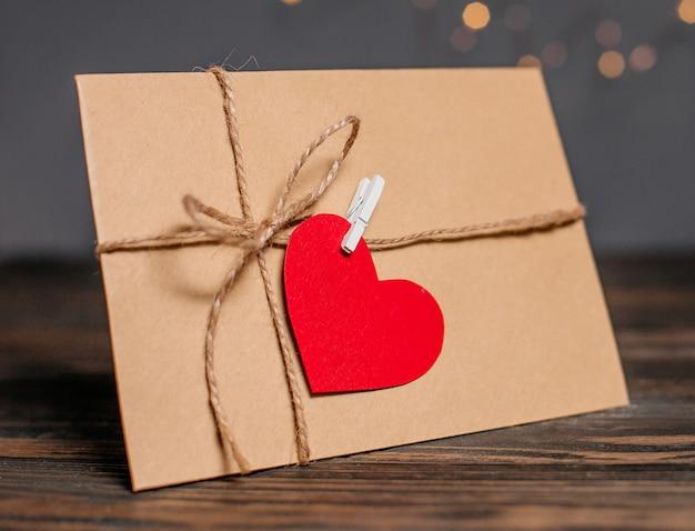 List miłosny z sercem na tle koncepcji światła, miłości i valentine na drewnianym stole