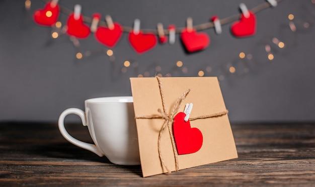 List miłosny z sercem obok filiżanki na tle koncepcji światła, miłości i valentine na drewnianym stole