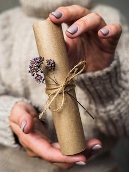 List ozdobiony kwiatem oregano w rękach dziewczynki