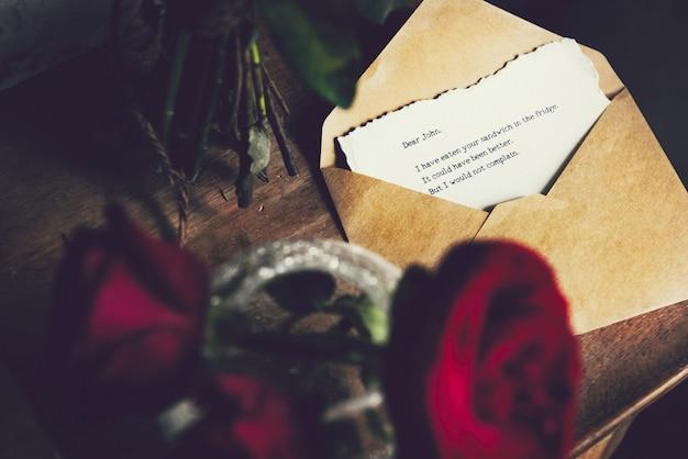 List z wazonem czerwonych róż