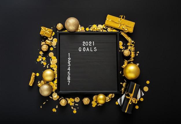 Lista celów na rok 2021 na czarnej tablicy z listami w ramce ze złotego świątecznego wystroju.