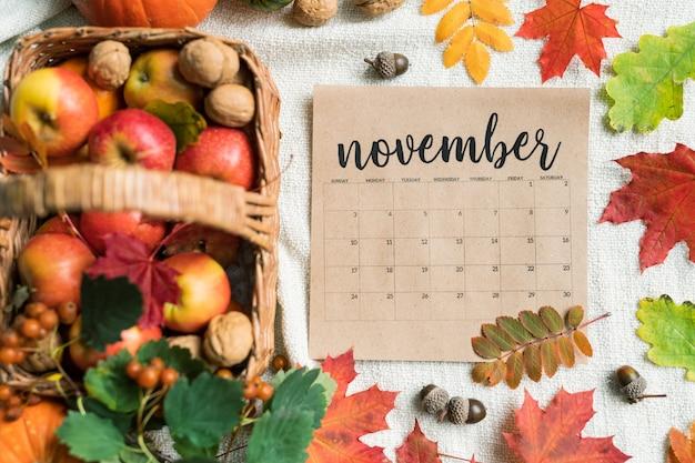 Lista kalendarza na listopad w otoczeniu dojrzałych jabłek, orzechów włoskich, żołędzi i kolorowych liści