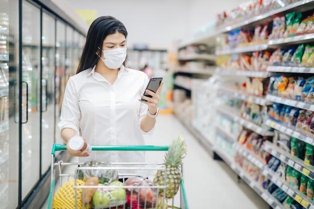 Lista kontrolna azjatyckiej kobiety za pomocą smartfona i zakupów z maską, bezpiecznie kupująca artykuły spożywcze, środki bezpieczeństwa w supermarkecie.