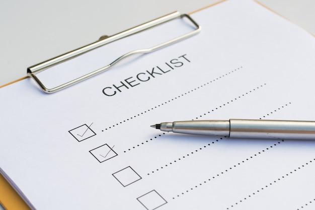 Lista kontrolna koncepcja - lista kontrolna, papier i pióro z listy kontrolnej słowo na drewnianym stole