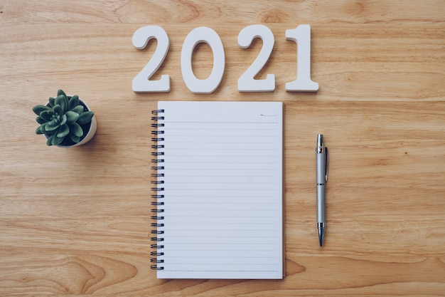Lista noworoczna 2021. biurko biurowe z notatnikami i pancilem z rośliną doniczkową.