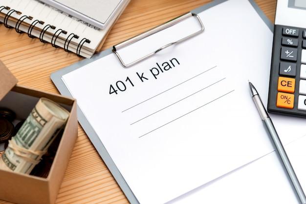 Lista planów 401 k z teczką, notatnikiem i kalkulatorem na drewnie.