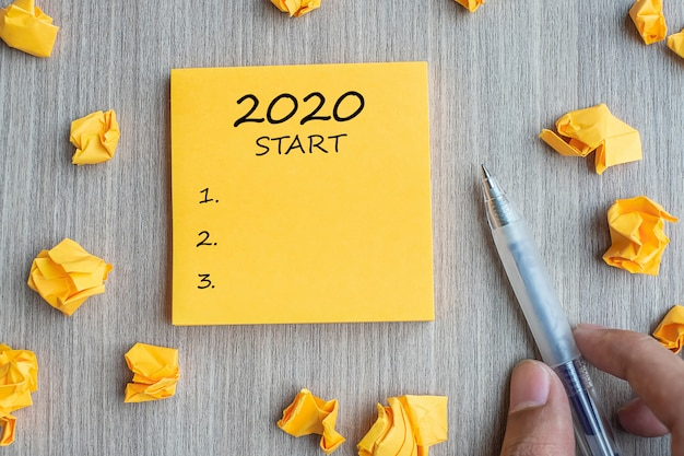 Lista początkowa 2020 na żółtej nucie z pomiętymi papierami i długopisem