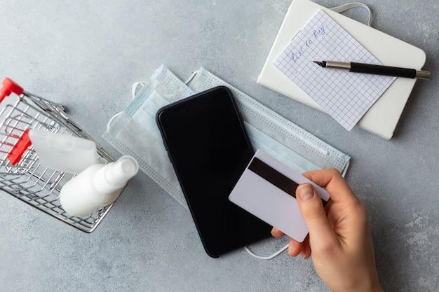 Lista zakupów na papierze toaletowym maska medyczna koncepcja wirusa corona wirus karta kredytowa mały kosz