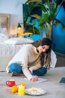 Lista życzeń. kobieta siedzi na podłodze i pisze swoją listę życzeń