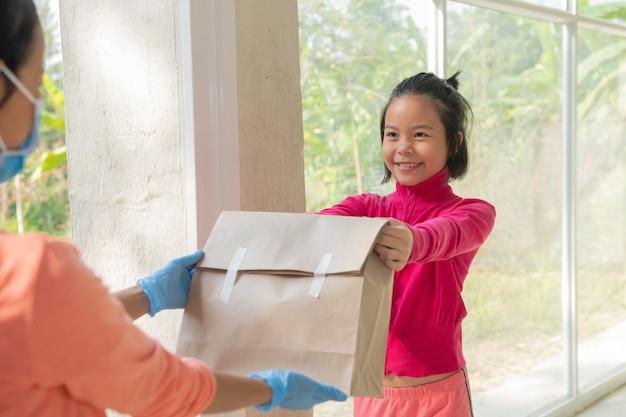 Listonosz, człowiek dostawy noszący maskę nosić małe pudełko dostarczyć klientowi przed drzwiami w domu. kobieta nosząca maskę zapobiega covid 19, wybuchowi zakażenia koronawirusem. koncepcja zakupy dostawy do domu.