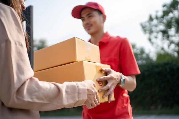 Listonosz przyniósł przesyłkę do domu z uśmiechem i radosną miną. młoda azjatycka kobieta bierze pudełko od listonosza przy drzwiach.