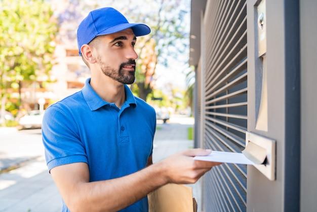 Listonosz umieszcza list w skrzynce pocztowej.