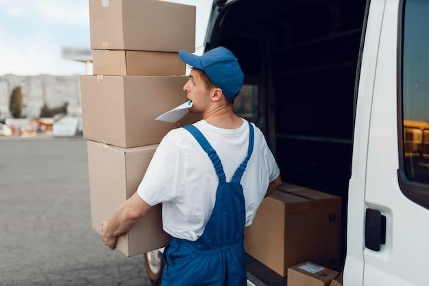 Listonosz w mundurze rozładowuje samochód z paczkami, firma kurierska. mężczyzna stojący przy kartonowych paczkach w pojeździe, mężczyzna dostawy, kurier lub wysyłka