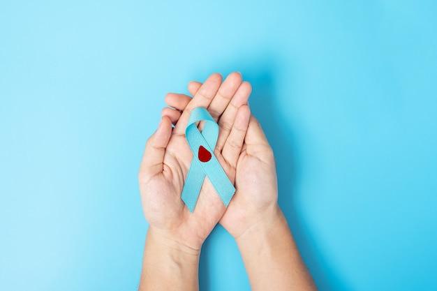 Listopad światowy dzień cukrzycy miesiąc świadomości, kobieta trzymająca jasnoniebieską wstążkę z kroplą krwi za wspieranie ludzi w życiu, profilaktyce i chorobach. opieki zdrowotnej, koncepcja dnia raka prostaty
