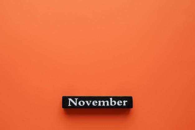 Listopadowe słowo na pomarańczowym tle