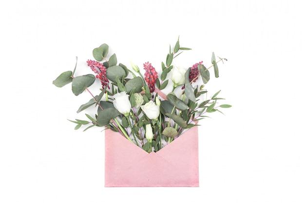 Listowa miłość. romantyczna koperta z kwiatami na stole. deklaracja uczuć miłosnych. widok z góry. zdjęcie w stylu instagram. kreatywna niezwykła kompozycja. leżał płasko, widok z góry