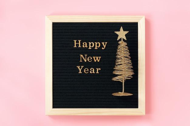 Listowa tablica z złotym tekstem szczęśliwego nowego roku i błyszczące choinki na różowej ścianie