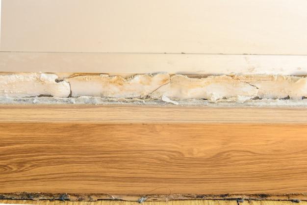 Listwy podłogowe i obrzęk koloru farby na starej białej ścianie