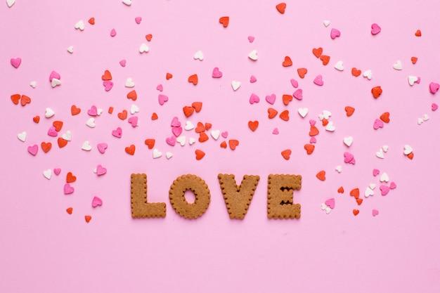 Listy ciasteczka miłość z różowymi i czerwonymi sercami na różowym