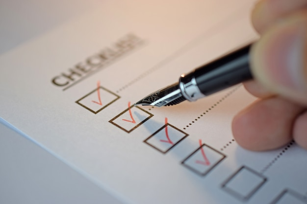 Listy kontrolnej pojęcie - listy kontrolnej pudełko z czerwonym znacznikiem wyboru, papierem i piórem z listy kontrolnej słowem na stole
