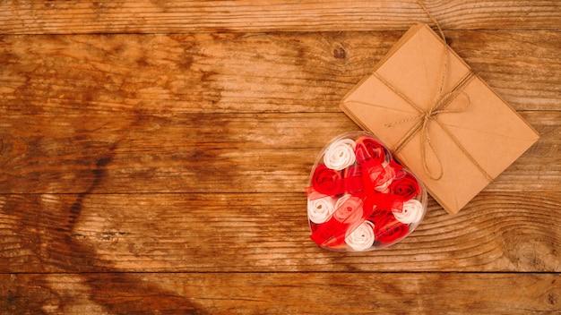 Listy w papierowych kopertach rzemieślniczych i prezent w postaci róż na drewnianym tle - widok z góry