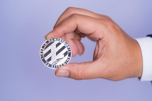 Litecoin ltc w zestawie z kryptowalutą na ręce biznesmena w niebieskim garniturze. zarchiwizuj i włóż i daj mi.