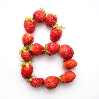 Litera b alfabetu angielskiego czerwonych świeżych truskawek na białym tle