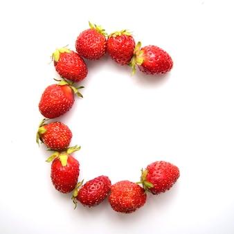 Litera c alfabetu angielskiego czerwonych świeżych truskawek na białym tle