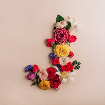 Litera j wykonana z prawdziwych naturalnych kwiatów na beżowym tle. czcionka kwiatowa. koncepcja kreatywna lato. widok z góry. płaskie ułożenie