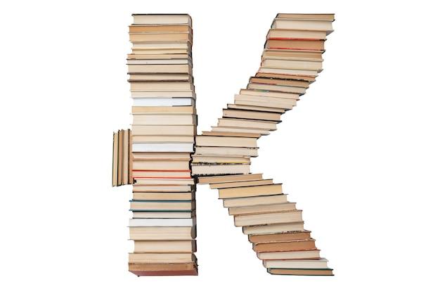 Litera k wykonana z książek na białym tle