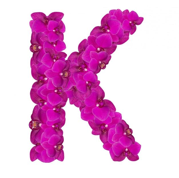 Litera k z płatków różowego kwiatu