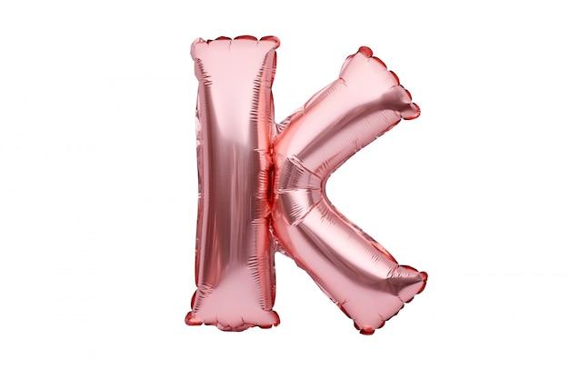 Litera k z różowego złotego nadmuchiwanego helu balonu na białym tle. balonowa czcionka w kolorze złotej różowej części pełnego zestawu alfabetu wielkich liter.