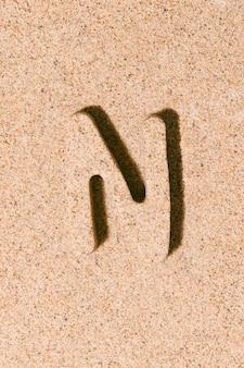 Litera n piasku na piasku na plaży koncepcja alfabetu letniego