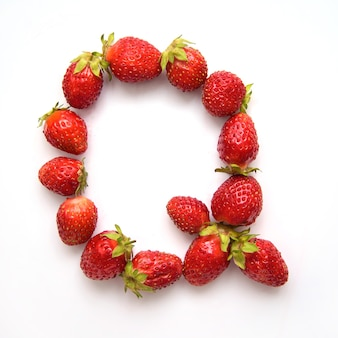 Litera q alfabetu angielskiego czerwonych świeżych truskawek na białym tle