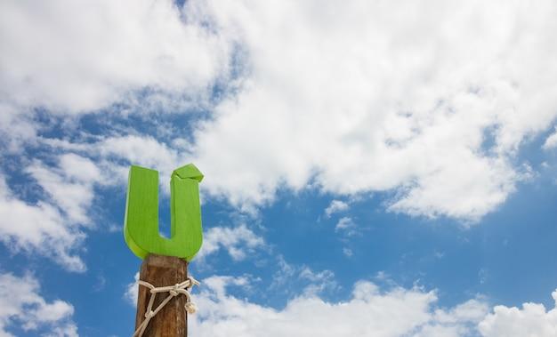 Litera u drewna przed błękitne niebo chmura