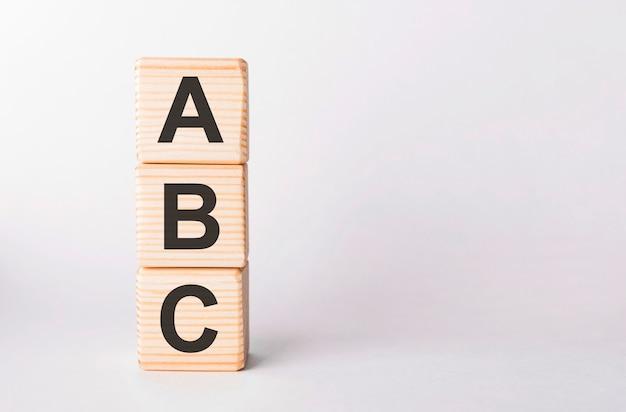 Litery abc drewnianych klocków w formie słupka na białym, kopia przestrzeń