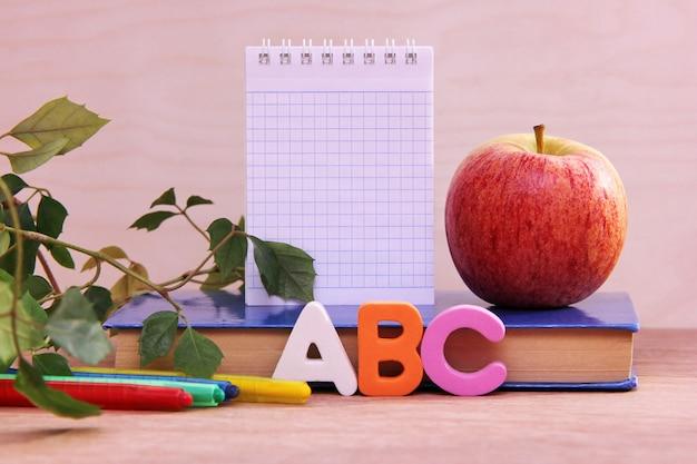 Litery abc w pobliżu książki i kolorowe kredki. dojrzałe jabłko i notatnik z miejscem do pisania na książce.