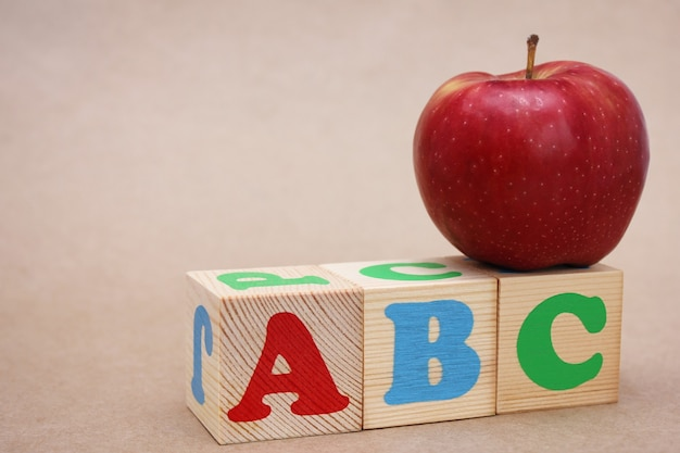 Litery alfabetu angielskiego abc i czerwone świeże jabłko na nich. pojęcie edukacji.