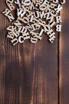 Litery alfabetu angielskiego na ciemnym tle drewnianych. pojęcie edukacji, gry słowne, robótki ręczne. miejsce na tekst