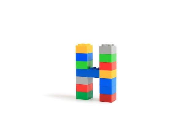 Litery alfabetu h od konstruktora kolorowych klocków z tworzywa sztucznego na białym tle. obraz ze ścieżką przycinającą