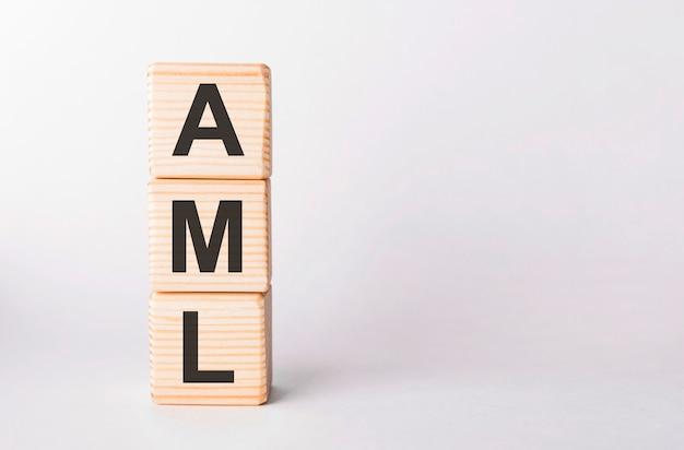 Litery aml z drewnianych klocków w formie słupków na białym tle