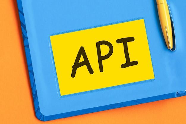 Litery api są napisane czarnymi literami na żółtym papierze firmowym