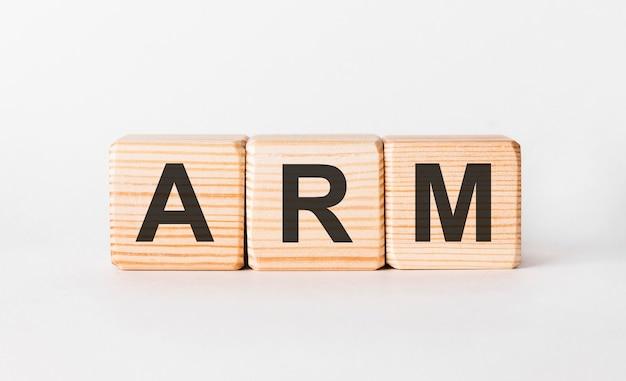 Litery arm z drewnianych klocków w formie słupka na białej, kopiowanej przestrzeni