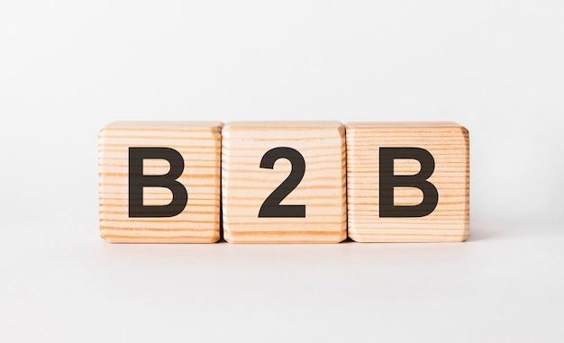 Litery b2b z klocków drewnianych w formie słupków na białym tle