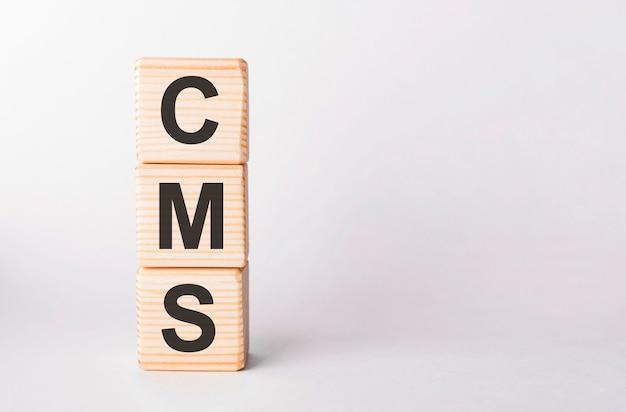 Litery cms z drewnianych klocków w formie słupków na białym tle