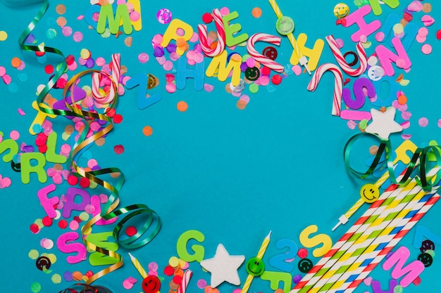 Litery, konfetti i serpentyny na niebieskim stole